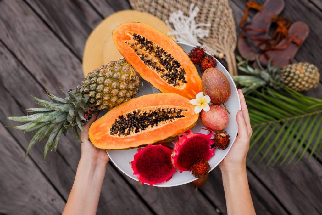 Женские руки с большой тарелкой свежих экзотических фруктов